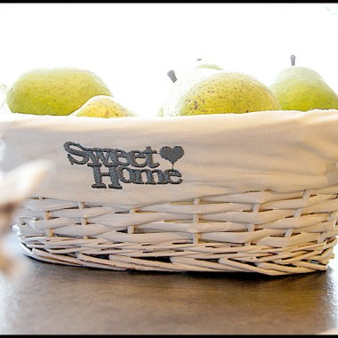 Owoce znalazły swoje miejsce w wiklinowym, białym koszyczku z wypełnieniem.