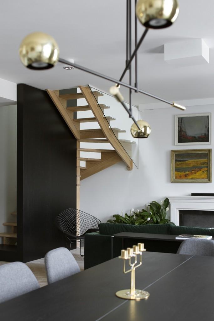 Domy i mieszkania, Apartament z prywatną biblioteką - Jedynym elementem pozostałym z dawnego wystroju są drewniane schody, które tylko odnowiono i zmodernizowano. Od strony salonu przesłania je czarna ścianka. Narożnik w odcieniu butelkowej zieleni (Sits/Nap) łagodnie przełamuje biało-szarą kolorystykę części wypoczynkowej. Stolik kawowy przy kanapie to projekt Poppyworks. Atrapa kominka stworzona ze sztukaterii nawiązuje do wykończenia dekoracyjnego ścian.
