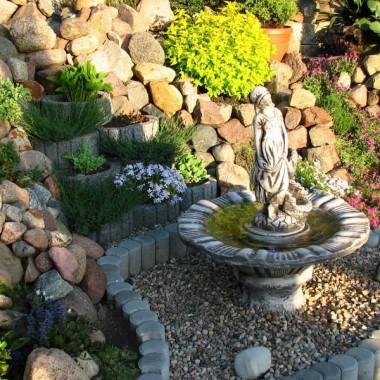 mała fontanna wkomponowana w skalniak