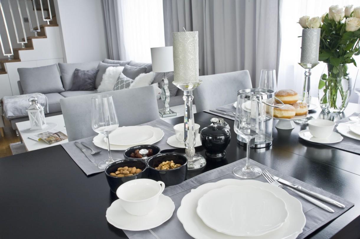 Domy i mieszkania, Ponadczasowe wnętrze w stylu modern classic - DOMOWA STREFA KOMFORTU Z holu trafiamy do części wypoczynkowej, której centralny punkt stanowi wygodna, nowoczesna kanapa. Puszyste poduszki, miękki dywan oraz dekoracyjne świeczniki i lampy sprawiają, że przestrzeń nabiera przytulności i ciepłego, domowego charakteru. Projektantka zadbała także o funkcjonalność wnętrza. Dzięki wykonanej na wymiar dyskretnej zabudowie, pod schodami powstała praktyczna szafka.