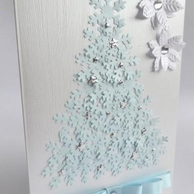 Cena: 7,00 złElegancka i nowoczesna kartka świąteczna&#x3B; utrzymana w błękitno-srebrzystej kolorystyce.Rozmiar po rozłożeniu to format zbliżony do A5, a złożona tworzy format C6, czyli ok 14,7x10,5cm.Kartka jest lekko przestrzenna, ozdobiona elementami dekoracyjnymi 3D, doskonale więc nadaje się zarówno do wysyłki, jak i do osobistego wręczenia np. idąc w świąteczne odwiedziny.Wykonana z grubego 215g papieru, w środku matowego śnieżnobiałego, a frontowa strona jest delikatnie fakturowana i metalizowana w kolorze srebrno-białym. Główną dekorację stanowi choinka uformowana z błękitnych, połyskujących śnieżek ozdobionych srebrnymi gwiazdkami, dwa perłowo-białe kwiaty poinsecji z cyrkoniami i wielowarstwowa błękitna 10mm nowoczesna kokarda.W środku znajdują się nadrukowane życzenia, do wyboru 8 wersji, otrzymają je Państwo po dokonaniu zakupu na adres mailowy lub pozostawią Państwo wybór mnie, wpisując to w wiadomości podczas zakupu.