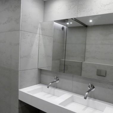 Beton architektoniczny - płyty betonowe na ścianie w łazience, w towarzystwie podwójnej umywalki z odpływem liniowym.Wyposażenie - LUXUM