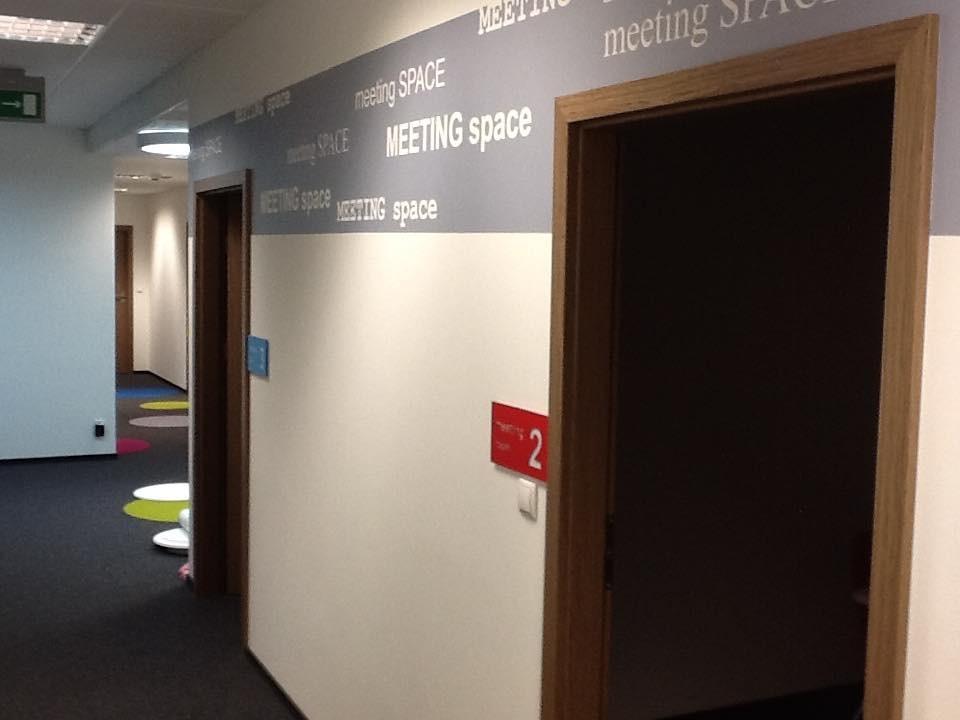 Gabinet, Kolorowe biuro Work Service Poznań - Widok na korytarz i ścianę zagospodarowaną naklejkami