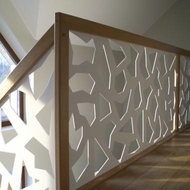 Schody dywanowe, wykonane z drewna dębowego - barwionego, balustrada wykonana z płyty stalowej w kolorze białym, na której zostały wycięte nieregularne figury geometryczne, całość zakończona drewnianym pochwytem w kolorze schodów