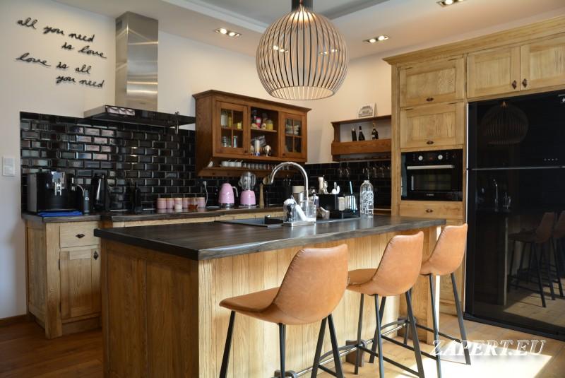 Kuchnia, Kuchnia z wyspą w stylu rustykalnym - Tę rustykalną kuchnię wykonaliśmy z jesionu. Zwarta zabudowa szafek jest w kształcie litery L. Na środku kuchni znajduje się wyspa, która pełni rolę nie tylko blatu roboczego, ale i stołu. Po drugiej stronie wysokiej zabudowy stoją dwie witryny ze stylowymi ramkami.  Nieregularny, wybarwiony na ciemno, drewniany blat szafek i wyspy, czarne cegły na ścianach oraz rustykalne uchwyty sprawiają, że wnętrze kuchni wygląda naprawdę ciekawie.