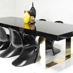 Awangardowy stół w wysokim połysku na nogach ze złotej stali.
