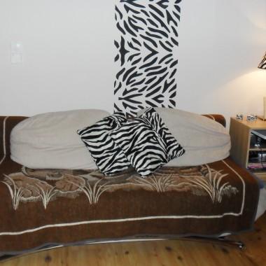 Motyw zebry na ścianie. Nie wiem jakie okrycie na kanapę dać. Na pewno nie zebrowe, bo będzie się zlewać dlatego elementem łączącym są poduszki w zebrę. Proszę o poradę.