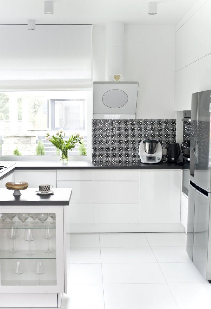 Domy i mieszkania, Ponadczasowe wnętrze w stylu modern classic - Charakter sypialni gospodarzy określa przyciągający wzrok obraz na ścianie ponad łóżkiem. Przytulny klimat wnętrza uzyskano łącząc złamaną biel i odcień taupe, dodatkowo podkreślone detalami w kolorze czerni i złota. W odróżnieniu od toalety dla gości łazienka gospodarzy jest bardzo jasna i lekka. To królestwo Pani domu. Wygodna, duża wanna pozwala zrelaksować się po ciężkim dniu, a eleganckie żyrandole, zdjęcia Marlin Monroe i czarne detale nadają wnętrzu kobiecy charakter. Wystrój dziecięcych pokoi dopasowano do wieku i zainteresowań młodych lokatorów.