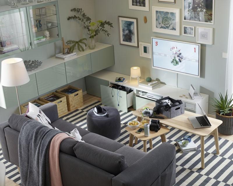 aranżacja kącika z telewizorem na ścianie i ramkami na zdjęcia zawieszonymi wokół telewizora, zielone szafki modułowe na wysoki połysk