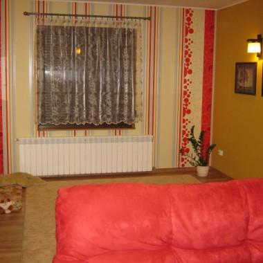 Pokój dzienny, narożnik w kolorze czerwonym, ściany w kolorze curry, meble brązowe z dodatkiem curry, beżowe panele, w podobnym odcieniu dywany, 1 okno i 1 drzwi tarasowe, 3 zdjęcia w dużym formacie w brązowej oprawie, w przyszłości przy oknie będzie stal stół i krzesła z kompletu mebli. Potrzebuję dobrego pomysłu właśnie na tę ścianę z oknem.