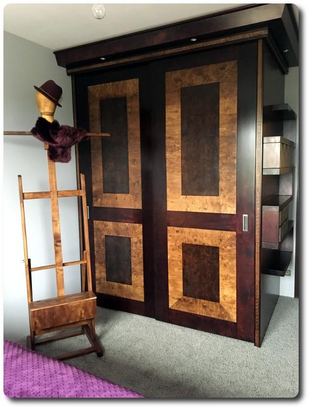 Garderoba, Szafy suwane z intarsją - Szafa z drzwiami suwanymi i intarsją.Wykonana z płyty stolarskiej,intarsja czeczota orzech z wstawką paska czarnego. Wyposażona w 2 pentografy oraz 12 szuflad z organizerami.