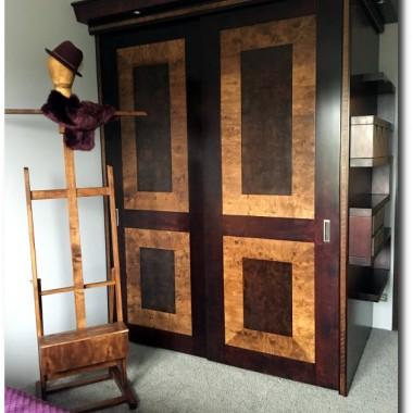 Szafa z drzwiami suwanymi i intarsją.Wykonana z płyty stolarskiej,intarsja czeczota orzech z wstawką paska czarnego.Wyposażona w 2 pentografy oraz 12 szuflad z organizerami.