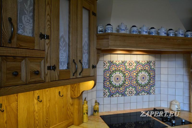 """Kuchnia, Kuchnia rustykalna """"z mozaiką"""" - Tę stylową kuchnię wykonaliśmy na zamówienie z jesionu. Jej ozdobą jest piekanik narożny z ozdobnym, murowanym okapem,który powstał również w naszej stolarni w Olsztynie. Wnętrze kuchni ożywia kolorowa mozaika, a rustykalne fronty ozdobione zazdroskami,  stylowymi uchwytami oraz zawiasami nadają meblom uroku ."""