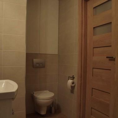 Widok na tron, a obok - na drzwi wejściowe do pomieszczenia. Musieliśmy zlikwidować dwie pary drzwi osobne do ubikacji, osobne do łazienki, a zamiast nich wstawić jedną parę, mniej więcej na środku ściany. Dla ciekawych: drzwi PORTA KONCEPT dąb klasyczny C2 60 cm z matowymi szybami i otworami wentylacyjnymi, ościeżnica bezprzylgowa ELEGANCE, klamka ACCENT srebro mat WC.