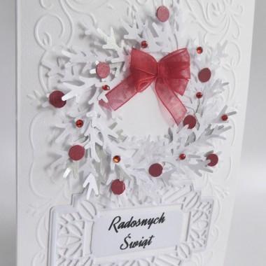 """Cena: 7,00 złElegancka i klasyczna kartka utrzymana w biało-czerwonej kolorystyce.Rozmiar po rozłożeniu to format zbliżony do A5, a złożona tworzy format C6, czyli ok 14,7x10,5cm.Wykonana z grubego 246g białego fakturowanego papieru, ozdobiona wieńcem z gałązek świerkowych, ozdobionym czerwoną kokardką, cyrkoniami i papierowymi """"bombkami"""" naklejonym na pięknie wytłoczonym papierze. Dodatkowo ozdobna, ażurowa ramka z napisem. Kartka jest lekko przestrzenna, ozdobiona elementami dekoracyjnymi 3D, doskonale więc nadaje się zarówno do wysyłki, jak i do osobistego wręczenia np. idąc w świąteczne odwiedziny.W środku znajdują się nadrukowane życzenia, do wyboru 8 wersji, otrzymają je Państwo po dokonaniu zakupu na adres mailowy lub pozostawią Państwo wybór mnie, wpisując to w wiadomości podczas zakupu."""