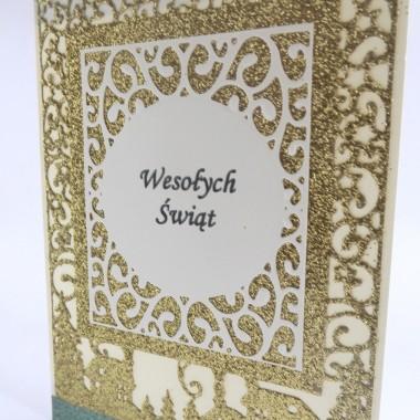 Cena: 8,00 złElegancka i klasyczna kartka utrzymana w biało-złotej kolorystyce.Rozmiar po rozłożeniu to format zbliżony do A5, a złożona tworzy format C6, czyli ok 14,7x10,5cm.Wykonana z grubego 230g kremowego papieru, bogato ozdobiona przepiękną i klimatyczną scenerią świąteczną wyciętą z grubego 300g złotego brokatowego papieru. Ponadto ozdobiona zielonymi brokatowymi wstawkami oraz efektowną ażurową dużą ramką z napisem. Kartka jest raczej płaska, doskonale więc nadaje się zarówno do wysyłki, jak i do osobistego wręczenia np. idąc w świąteczne odwiedziny.W środku znajdują się nadrukowane życzenia, do wyboru 8 wersji, otrzymają je Państwo po dokonaniu zakupu na adres mailowy lub pozostawią Państwo wybór mnie, wpisując to w wiadomości podczas zakupu.