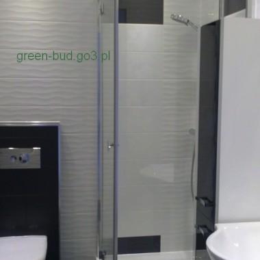Łazienka mała tzw. blokowa. Wykonana w stylu nowoczesnym. Biały motyw na ścianie w brodziku, czarny koło wc. Piękna falowa płytka.