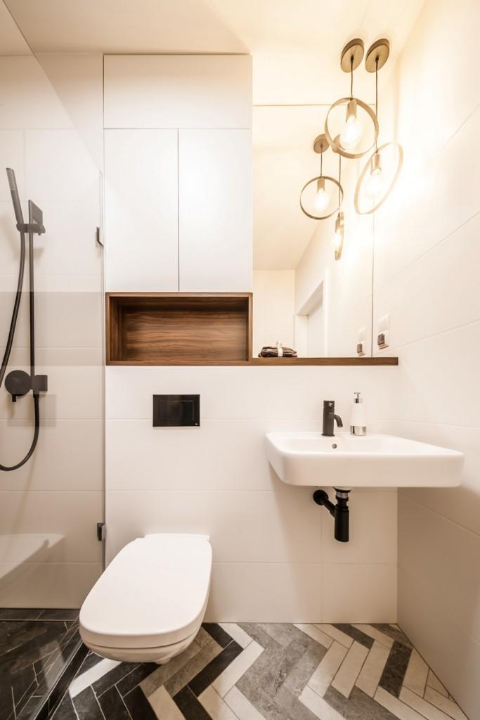 Domy i mieszkania, Szarość, mat i jodła – oryginalne i nowoczesne wnętrze - Łazienka w jodełkę Motyw jodełki zastosowano także w projekcie łazienki, dzięki czemu współgra stylistycznie z pozostałą częścią mieszkania. Znajdziemy w niej zarówno kontrasty, złożone z bieli oraz różnych odcieni szarości, jak i drewniane akcenty. Największą uwagę w aranżacji łazienki przykuwa wydzielona szklaną taflą strefa prysznicowa. Do jej stworzenia wykorzystano ciemnoszare płytki, które ułożono w klasyczną jodełkę, pokrywając podłogę oraz jedną ze ścian. W efekcie otrzymano niebanalną kabinę, kontrastowo odcinającą się od reszty pomieszczenia, utrzymanej w jaśniejszej tonacji.