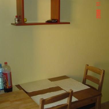 Przy 2 ścianie stoi stół z deską do krojeniai jasnymi podkładkami. Nad nim wisi pólka z doniczkowymi kwiatami