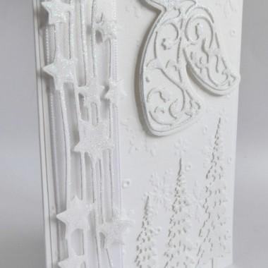 Cena: 10,00 złElegancka i klasyczna kartka świąteczna&#x3B; utrzymana w białej kolorystyce.Rozmiar po rozłożeniu to format zbliżony do A5, a złożona tworzy format C6, czyli ok 14,7x10,5cm.Wykonana z białego grubego 246g fakturowanego papieru, na froncie naklejono ten sam papier dodatkowo efektownie wytłoczony, a na nim znajdują się naklejone w technice 3D oprószone białym brokatem świąteczne dekoracje. Kartka jest lekko przestrzenna, ozdobiona elementami dekoracyjnymi 3D, doskonale więc nadaje się zarówno do wysyłki, jak i do osobistego wręczenia np. idąc w świąteczne odwiedziny.W środku znajdują się nadrukowane życzenia, do wyboru 8 wersji, otrzymają je Państwo po dokonaniu zakupu na adres mailowy lub pozostawią Państwo wybór mnie, wpisując to w wiadomości podczas zakupu.