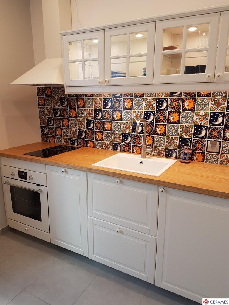 Kuchnia, Burza kolorów na kuchennej ścianie - Zaprezentowana na zdjęciu, zwyczajna w swej formie, aranżacja kuchenna zdaje się na pozór niczym nie odbiegać od obecnych projektów. Tymczasem jest jeden zasadniczy akcent, który sprawia, że pomieszczenie nabiera nietuzinkowego i niepowtarzalnego charakteru. Efekt ten uzyskano dzięki zastosowanej  glazurze.  Możemy podziwiać meksykańskie kafle takie jak chociażby Elvira czy Flores.