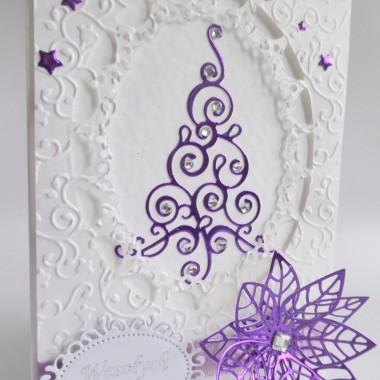 Cena: 10,00 złElegancka i nowoczesna kartka świąteczna&#x3B; utrzymana w białej-fioletowej kolorystyce.Rozmiar po rozłożeniu to format zbliżony do A5, a złożona tworzy format C6, czyli ok 14,7x10,5cm.Wykonana z grubego 246g fakturowanego białego papieru, ozdobionego w technice 3D pięknie wytłoczonym tłem z wyciętą efektowną ramką. Całości dopełniają ozdoby z fioletowego lustrzanego papieru, cyrkonie, oraz ozdobna ramka z wysrebrzonym napisem. Kartka jest przestrzenna, ozdobiona elementami dekoracyjnymi 3D, doskonale więc nadaje się do osobistego wręczenia np. idąc w świąteczne odwiedziny.W środku znajdują się nadrukowane życzenia, do wyboru 8 wersji, otrzymają je Państwo po dokonaniu zakupu na adres mailowy lub pozostawią Państwo wybór mnie, wpisując to w wiadomości podczas zakupu.