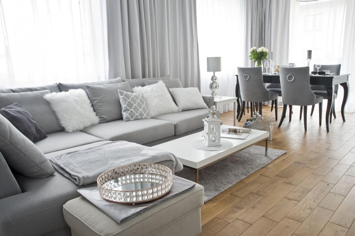 Domy i mieszkania, Ponadczasowe wnętrze w stylu modern classic - Parter domu tworzy zaaranżowana w otwartym planie część dzienna. Dominuje stonowana, lecz nie zimna, jasna kolorystyka oparta o paletę bieli i szarości. Styl wnętrza określa ulokowana w wejściu do salonu elegancka konsola. Lekka forma, lustrzane powierzchnie i delikatne, kryształowe uchwyty nie pozostawiają wątpliwości, że w tym domu króluje modern classic.