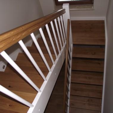 schody drewniane, wykonane w połączeniu dwóch kolorów, konstrukcja biała, stopnie w naturalnym kolorze drewna.