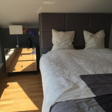 Łóżko z tapicerowanym zagłówkiem zajęło wnękę pod skosem.
