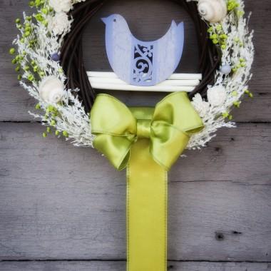 Wiosenna dekoracja w formie wiszącego wiankana brązowej naturalnej bazie z wikliny.Połączenie zieleni, fioletu oraz pastelowego kremu suszonychtraw i patyków wprowadzą powiew radosnej świeżości do każdego wnętrza.