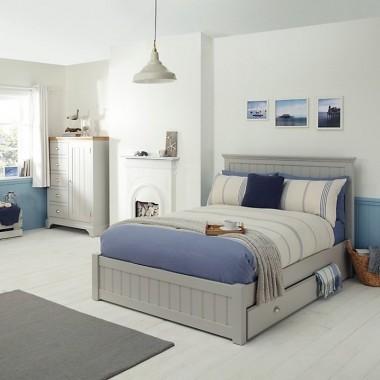 Szare łóżko w stylu skandynawskim stanowi kompromis w przypadku braku zgody na sypialnię w całości urządzonej na biało. Stylowa szarość łóżka Suzi jest uzupełniona praktycznym elementem w postawi szuflad. Pozostałe elementy są utrzymane w szarości, fiolecie i odcieniach niebieskiego. Meble powstały w pracowni meblarnia.com.pl