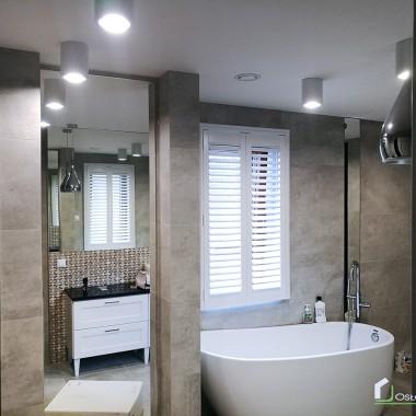 Białe okiennice drewniane w łazience.