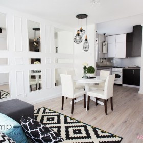 Salon z aneksem, lustrzanymi ścianami i lampami druciakami