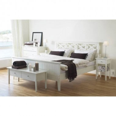 Minimalistyczna sypialnia, urządzona w skandynawskim stylu. W centrum łóżko Laura, obok postawiono stoliki nocne Laura na wysokich nóżkach. W nogach łóżka - niska komoda Laura, która służy również jako stolik. Meble pochodzą z pracowni meblarnia.com.pl.