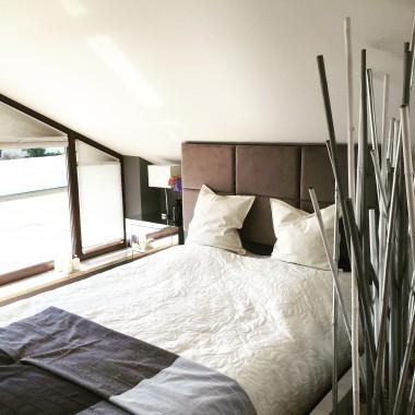 Sypialnia na poddaszu. Łóżko z tapicerowanym zagłówkiem. Dekoracja z bambusowych tyczek.