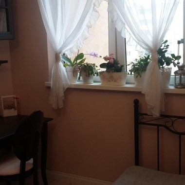 Kolor ścian - pudrowy róż, styl rustykalny, białe panele deski, łóżko kute czarne, zegar dworcowy