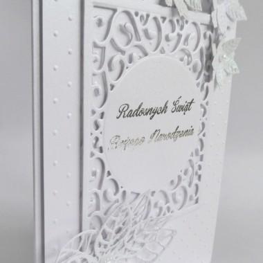Cena: 11,00 złElegancka i klasyczna kartka świąteczna&#x3B; utrzymana w ponadczasowych odcieniach bieli.Rozmiar po rozłożeniu to format zbliżony do A5, a złożona tworzy format C6, czyli ok 14,7x10,5cm.Wykonana z przepięknego grubego 250g perłowo-białego papieru. Na nim naklejono techniką 3D ten sam papier pięknie wytłoczony i efektowną ażurową ramkę z wysrebrzonym napisem. Całości dopełniają 4 poinsecje w odcieniach bieli oprószone dodatkowo białym brokatem. Kartka jest przestrzenna, doskonale więc nadaje się do osobistego wręczenia np. idąc w świąteczne odwiedziny.W środku znajdują się nadrukowane życzenia, do wyboru 8 wersji, otrzymają je Państwo po dokonaniu zakupu na adres mailowy lub pozostawią Państwo wybór mnie, wpisując to w wiadomości podczas zakupu.