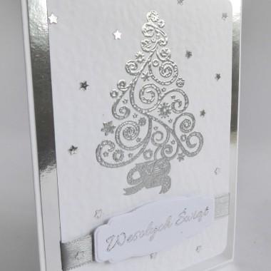 Cena: 9,00 złElegancka i nowoczesna kartka utrzymana w srebrno-białej kolorystyce.Rozmiar po rozłożeniu to format zbliżony do A5, a złożona tworzy format C6, czyli ok 14,7x10,5cm.Wykonana z grubego 246g białego fakturowanego papieru, na którym naklejono srebrny lustrzany papier i na nim ponownie biały, który dodatkowo został udekorowany piękną wypukłą srebrną choinką, gwiazdkami, 12mm wstążką oraz wysrebrzonym napisem.Kartka jest raczej płaska, doskonale więc nadaje się zarówno do wysyłki, jak i do osobistego wręczenia np. idąc w świąteczne odwiedziny.W środku znajdują się nadrukowane życzenia, do wyboru 8 wersji, otrzymają je Państwo po dokonaniu zakupu na adres mailowy lub pozostawią Państwo wybór mnie, wpisując to w wiadomości podczas zakupu.