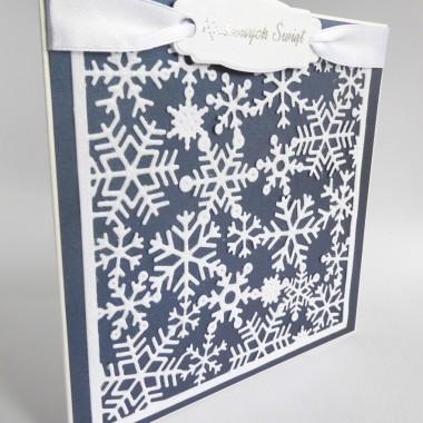 Cena: 8,00 złElegancka i nowoczesna kartka świąteczna utrzymana w biało-granatowej tonacji.Rozmiar po rozłożeniu to ok 30x15 cm, a złożona tworzy kwadrat o boku ok 15cm.Wykonana z grubego 215g papieru w środku śnieżnobiałego, a na froncie delikatnie fakturowanego i metalizowanego w kolorze biało-srebrnym. Ponadto znajduje się tam ciemnoniebieskie tło z perłowego papieru będące doskonałym kontrastem dla białego tła śnieżynkowego oprószonego białym holograficznym brokatem. Kartka przepasana jest efektownie białą 17mm wstążką i ramką z wysrebrzonym napisem.Kartka jest przestrzenna, zdobiona elementami 3D, idealna zarówno do wysłania, jak i do osobistego wręczenia np. idąc w świąteczne odwiedziny.W środku znajdują się nadrukowane życzenia, do wyboru 7 wersji, otrzymają je Państwo po dokonaniu zakupu na adres mailowy lub pozostawią Państwo wybór mnie, wpisując to w wiadomości podczas zakupu.