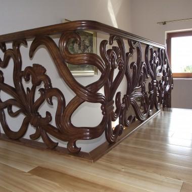 Schody z drewna na konstrukcji betonowej, wykonane z drewna jesionowego,barwionego.Balustrada drewniana, ręcznie rzeźbiona.