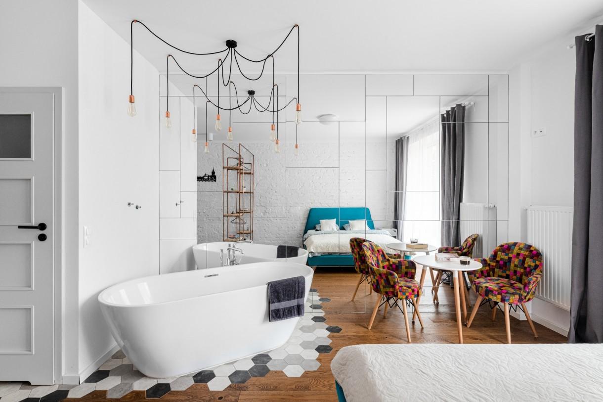 Domy i mieszkania, Klimatyczna oaza w samym centrum Warszawy - Zjawiskowa, lustrzana ściana dodatkowo eksponuje wannę, ale przede wszystkim optycznie powiększa wnętrze i podkreśla inspirację stylem glamour. W trakcie prac wykończeniowych wykonawcy odkryli piękną cegłę, którą spontanicznie pokryto białą farbą, zachowując urok detalu kojarzonego z kamienicami.