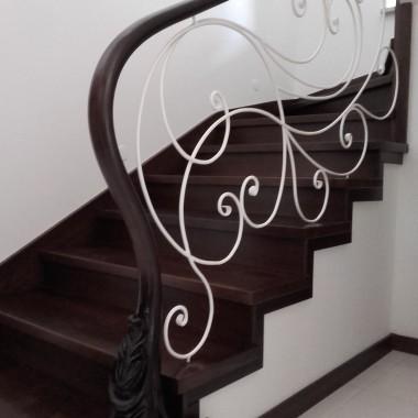 Schody zabiegowe wykonane z drewna dębowego, barwionego na ciemny orzech.Balustrada  metaloplastyka, pomalowana proszkowo na biało, poręcz drewniana w kolorze schodów, konstrukcja schodów betonowa.