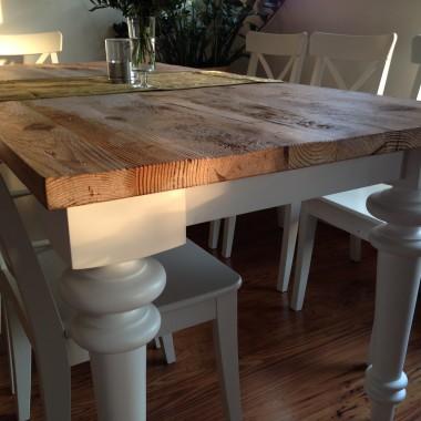 Stół z blatem ze starego drewna. Blat osadzony na białych toczonych nogach pomalowanych na biało.
