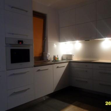 Pokój dzienny z aneksem kuchennym, meble biały lakier, pod szafkami biały lakobel, blat orzechowy. Aneks kuchenny narazie na surowo, będą jeszcze karnisze, więc i firanki, może jakiś dywan. Stolik kawowy też jest najlepszy tymczasowy lack, z poprzedniego mieszkania, docelowo ma byc jakiś biały.
