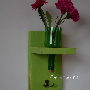 Kwietnik wykonany ręcznie w dwóch kolorach. Zamiast kwiatów można włożyć świecę, która wieczorem subtelnie rozświetli butelkę, a przy tym pomieszczenie. Deska jest delikatnie przetarta, ale także niezbyt mocno szlifowana, aby pozostawić strukturę drewna. Krawędzie butelek zabezpieczone. Poprzez zamontowane haczyki można używać go jako małego wieszaka na klucze.