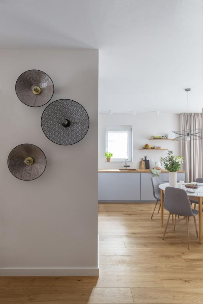 Domy i mieszkania, Mieszkanie na Białołęce w kolorach roku 2021 - Lekko i efektownie Niespełna 70-metrowe mieszkanie położone jest na parterze, dlatego jednym z ważniejszych zadań, przed którymi stanęli projektanci Decoroom było odpowiednie zaplanowanie oświetlenia. We wszystkich pomieszczeniach, poza sypialnią, na suficie rozmieszczono dyskretne reflektorki w białej oprawie, które równomiernie oświetlają przestrzeń.