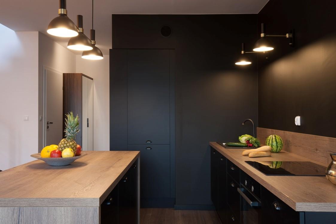 Domy i mieszkania, Szarość, mat i jodła – oryginalne i nowoczesne wnętrze - W kuchni dominują ciemne barwy, a całość aranżacji ożywia blask światła rzucanego przez lampy. Fronty mebli utrzymane zostały w kolorze ściany, dzięki czemu stały się niemal niewidoczne. Warto zwrócić uwagę na matowe wykończenia, które podkreślają i wydobywają dodatkowo surowy charakter drewna – mówi Lena Kwietniewska, architekt pracowni KODO Projekty i Realizacje.
