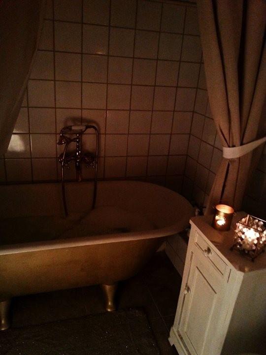 Łazienka, Retro łazienka z kominkiem - Wanna po bokach ma zasłony, za jedną z nich jest półka z kosmetykami w dozownikach. Na zdjęciu nie widać ale nad wanną jest drążek prysznicowy i zasłona do niego jest schowana za drugą lnianą zasłoną. Jak potrzebuję skorzystać z prysznica to ją rozsuwam i mam kabinę prysznicową w angielskim stylu czyli taką owalną na wielkość wanny, czyli większą niż standardowy brodzik. Dlatego też są płytki za wanną (z odzysku, stare, ecri popękane, odnowione i przyklejone), Za wanną skośna ścianka aby woda spływała. Druga zasłona zasłania też grzejnik na wodę.