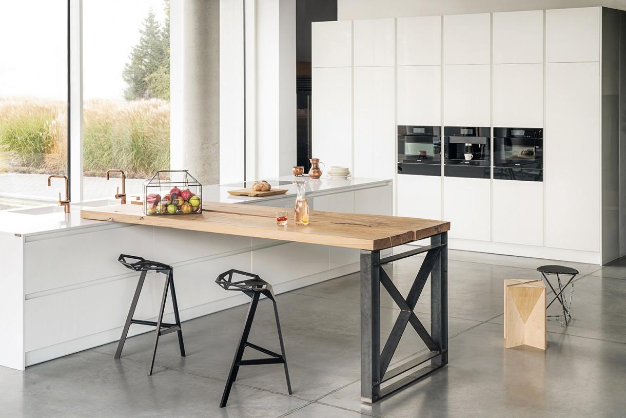 Kuchnia, Kuchnia zanurzona w bieli - Biel, która łączy Biel jest jednym z ulubionych kolorów minimalistów. Prowokuje do poszukiwania piękna w prostocie, czytelnych rozwiązaniach aranżacyjnych. Eleganckich, nie pozbawionych też charakteru. Kolor ten idealnie współgra zarówno z drewnem, jak i kamieniem, a dane połączenie albo wzmacnia poczucie świeżości, albo przeciwnie – delikatnie gasi czy przełamuje jej czystość i nieskazitelność.