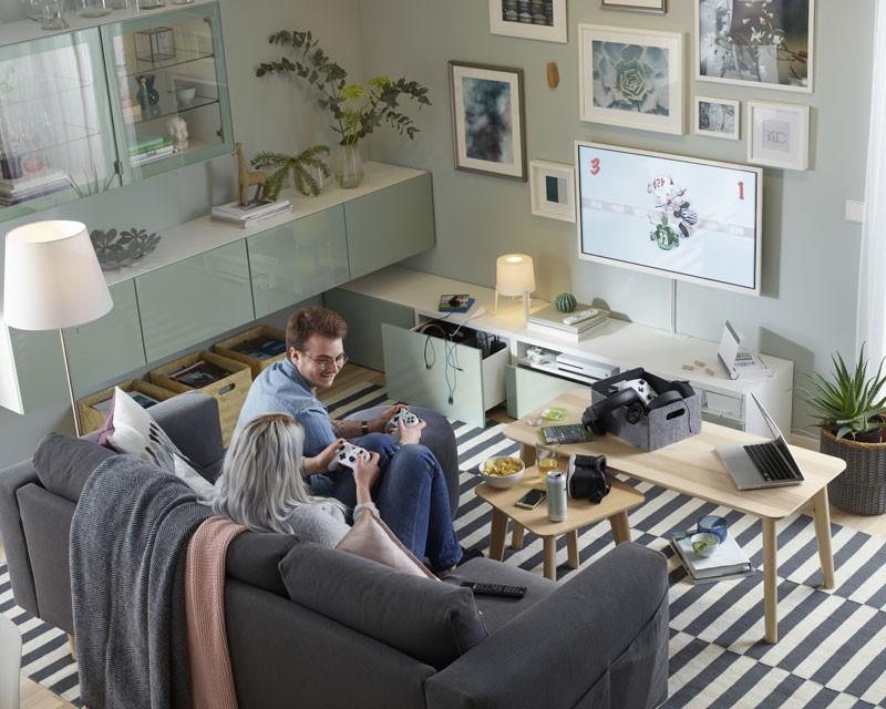 Ściana z telewizorem w białej ramie a nad nią zdjęcia i obrazki